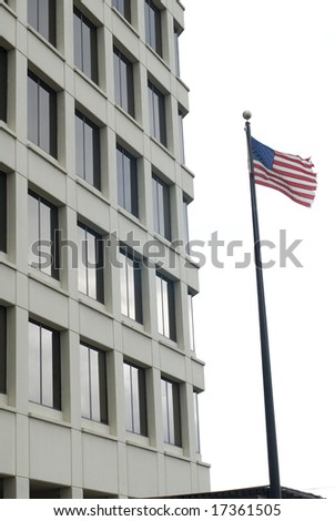 American flag waving outside of a tall cream building