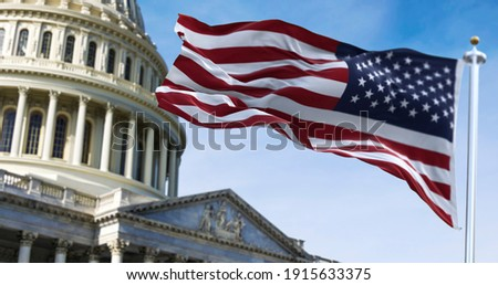 American flag waving with the US Capitol Hill in the background Foto stock ©