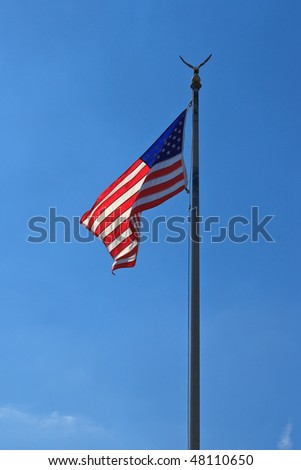 American flag, with globe and eagle, waving against blue sky, back lit. Portrait orientation.