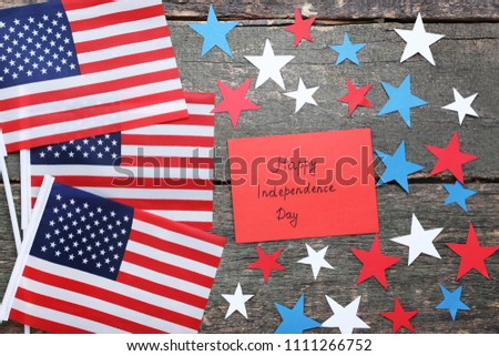 American flags and paper with inscription Happy Inscription Day on wooden table #1111266752