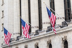 American flags on exterior facade of New york Stock Exchange, largest stock exchange in world by market capitalization and most powerful global financial institute. Wall street, New York City, USA.