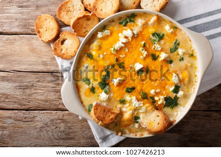 American food: hot chicken buffalo dip close-up in a baking dish with toasted bread on the table. Horizontal top view from above