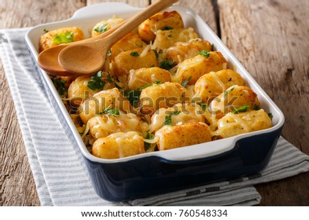 American Food: Tater Tots with cheese, meat, corn and parsley close-up in a baking dish on the table. horizontal