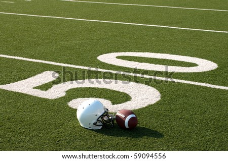 American football and helmet on field next to 50 yard line.