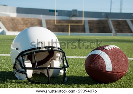 American football and helmet on field with goal post in background.