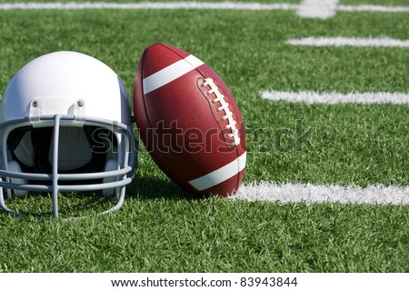American Football and Helmet on the Field - stock photo