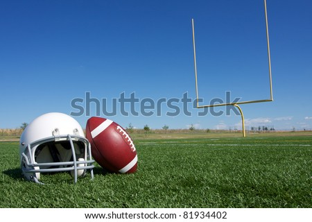 American Football and Helmet on the Field with Goal Posts in the background