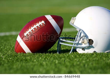 American Football and Helmet on the Field with shallow depth of field