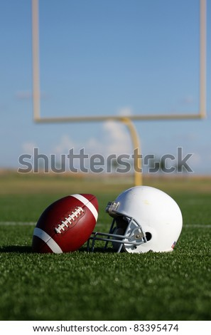 American Football and Helmet with the Goal Posts in the background