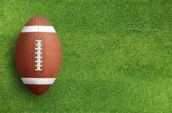 American football ball on green grass field background.