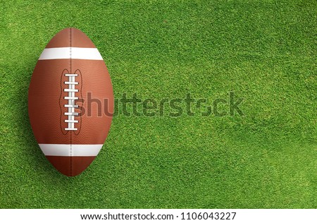 American football ball on green grass field background.