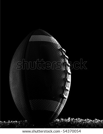 American football close up at night on flood lit green field (dark mood) in kicking position black and white