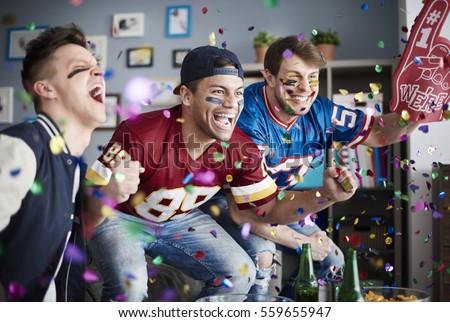 American football fans among falling confetti #559655947
