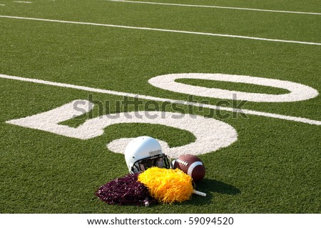 American football, helmet, and pom poms on field next to 50 yard line.