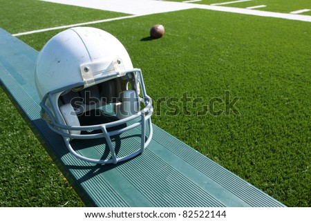 American Football Helmet on the Bench with ball and field in the background