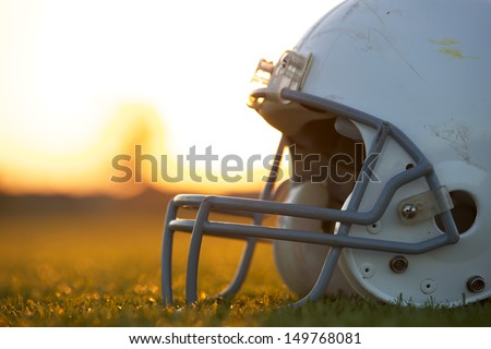 American Football Helmet on the Field at Sunset with room for copy