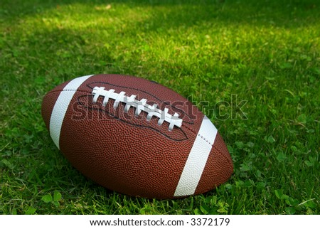 American football isolated on top of green grass