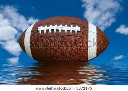 American football isolated over a cloudy sky background with water reflection