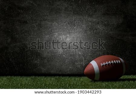American football on green grass, on dark background. Team sport concept