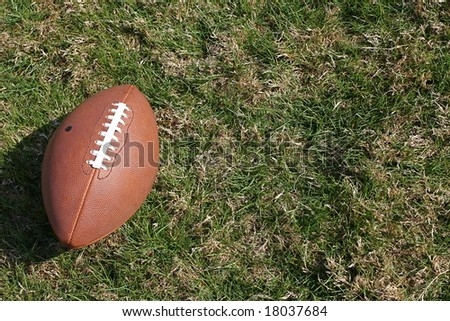American football on rough grass