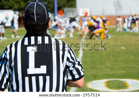 American Football played by young men with game official linesman referee - stock photo