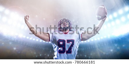 american football player celebrating after scoring a touchdown on big modern stadium field with lights and flares at night #780666181