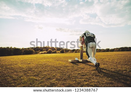 American football player doing tackle drills with a tackle sled outside on a sports field during an afternoon practice #1234388767