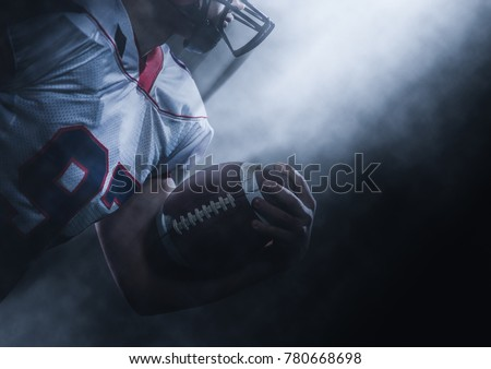 American football player holding ball while running on field at night #780668698