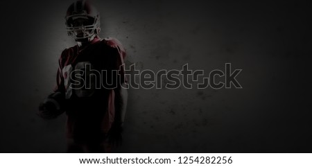 American football player in helmet holding rugby ball against old weathered wall