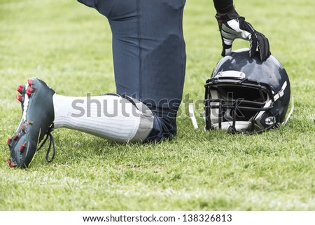 American football player kneels on the playground