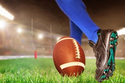 American football player prepares to kick ball for conversion points or field goal in brightly lit outdoor stadium with focus on foreground and shallow depth of field on background.