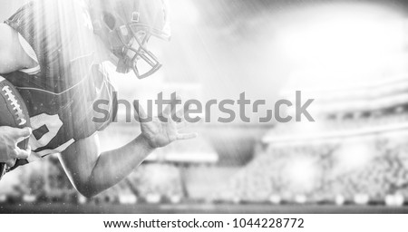 American football Player running with the ball isolated on big modern stadium field with lights and flares #1044228772