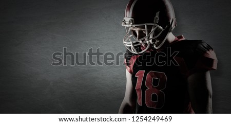 American football player standing in rugby helmet against old weathered wall