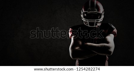 American football player standing with arms crossed against old wall background