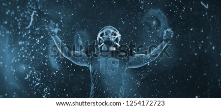 American football player standing with arms up against old weathered wall
