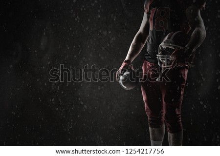 American football player standing with helmet and rugby ball against old wall background