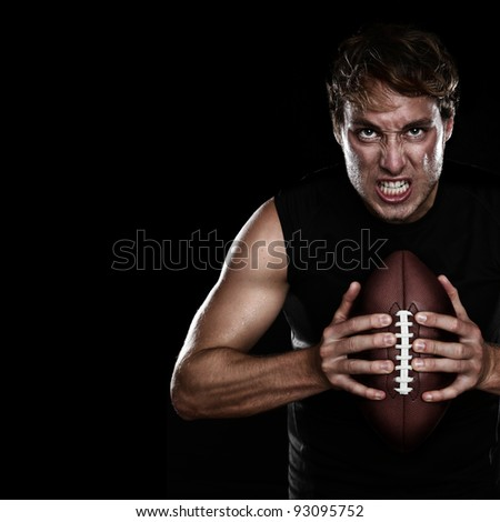 American football player staring aggressive holding american football on black background. Strong fit Caucasian fitness man with black copy space.