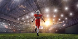 American football players on professional stadium on sunset.