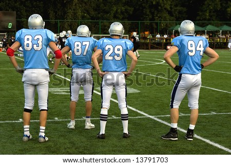 American football players on sidelines at a game field.