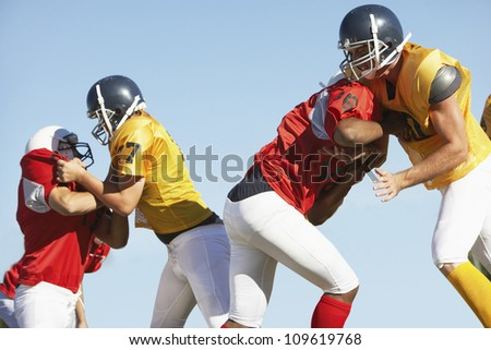 American football players tackling each other against clear sky
