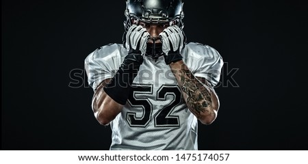 American football sportsman player in helmet isolated on black background. Sport and motivation wallpaper.