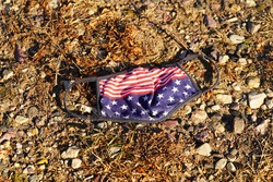 American freedom face mask laying on the ground showing disgrace.