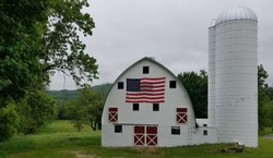 American Holiday Spirit with a Rustic, White Patriotic Barn and Silo, in Hillside Country Woodland Setting, Surrounded by Trees; America, USA, Patriotism, Be Thankful