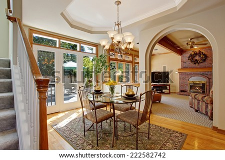 American house interior. Bright dining area with walkout patio in luxury house. DIning glass table with chairs