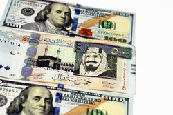 American hundred dollars bill and Saudi Arabia riyals currency banknotes of five hundred 500 Saudi Riyals, Saudi Arabia money and American dollars currencies exchange rate isolated on white background