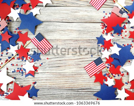 American independence Day, celebration, patriotism and holidays concept - flags and stars on the 4th of July party on top on wooden background #1063369676