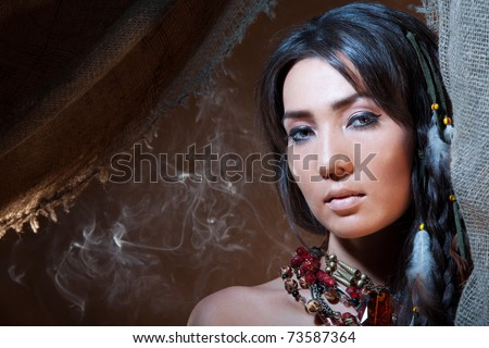 American Indian fortune teller looking from a tent with a smoke - studio photo with professional makeup