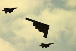 American large stealth bomber escorted by two small fighter planes