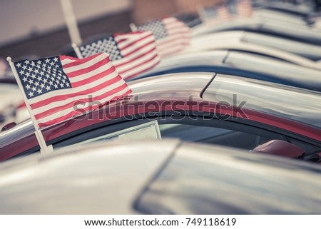 American Made Cars Sale Concept Photo. United States Economy and Market Theme. Brand New Vehicles For Sale with American Flags Attached. Dealership Lot.