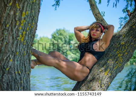 American mature bodybuilder woman. Sport style in modern life of urban woman. Fit lifestyle, Lady sport figure demonstrates her body at park #1155743149